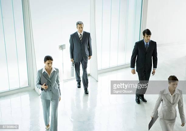 Four executives entering office building lobby