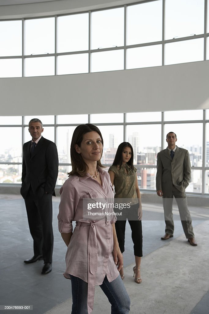 Four executives in empty office (focus on woman in foreground) : Stock Photo
