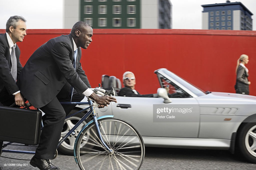 Four executives in front of red wall, one walking, one in car and two on tandem bike : Stock Photo