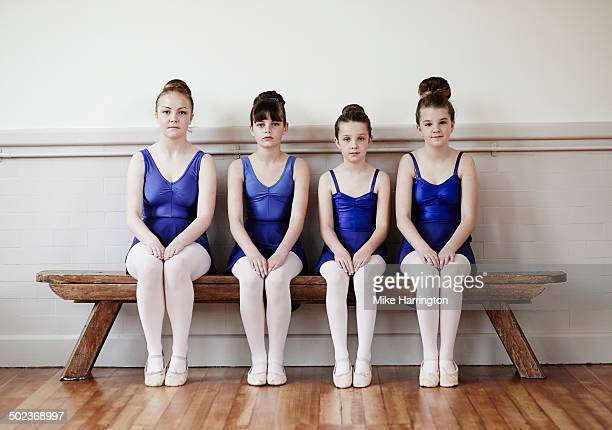 Four female ballet dancers sitting on bench.