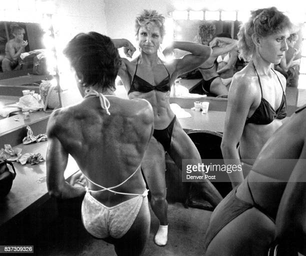Four female bodybuilders primped in front of mirrors in a tiny dressing room backstage before final competition in Golden Saturday evening From left...