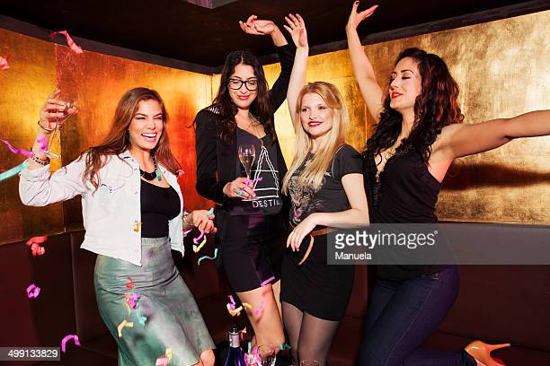 Four female friends celebrating in nightclub