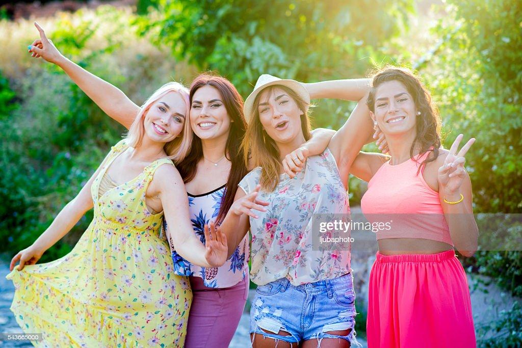 Cuatro mujeres amigos divirtiéndose en día de verano al aire libre : Foto de stock
