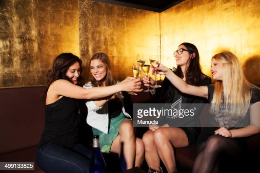 Four female friends toasting with wine in nightclub