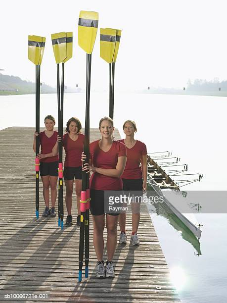 Four female rowers standing on pier holding oars