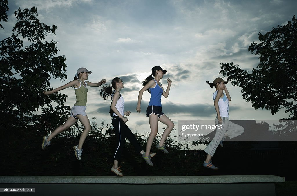 Four female runners leaping in air, side view : Stock Photo