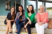 Four female teachers sitting on steps at entrance of school