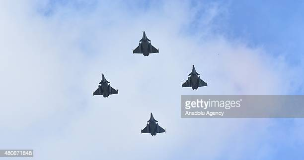 Four French Air Force Rafale C fighter jets fly over the ChampsElysees avenue during the Republic Day on the Champs Elysees in Paris France on July...