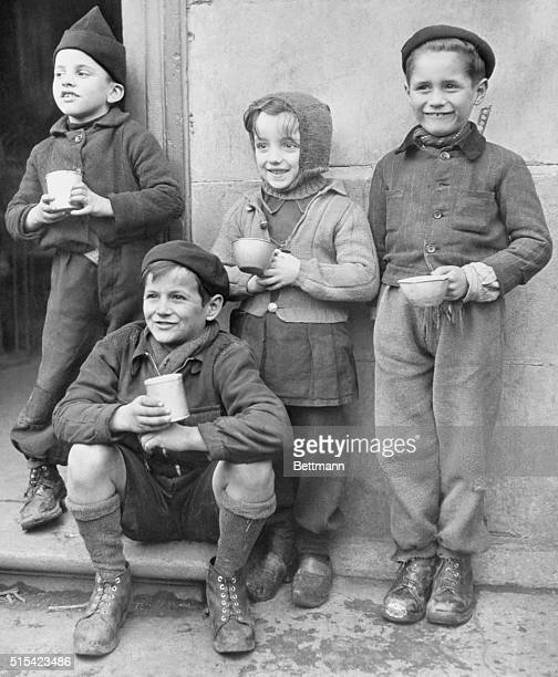 Four French children eagerly await their daily ration of powered milk their first since before the war The American Red Cross is distributing powered...
