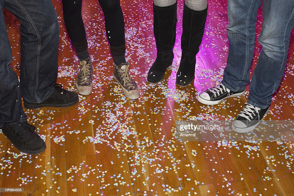 Four friends at a party with confetti, low section : Stock Photo