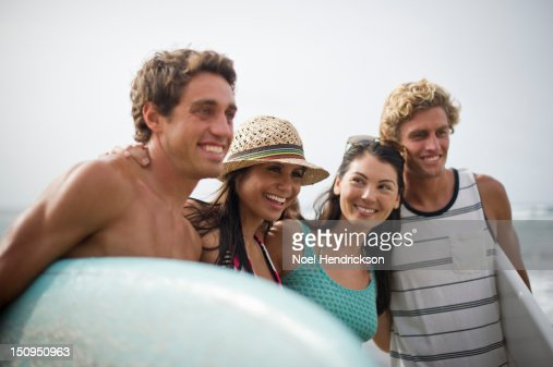 Four friends at the beach embrace for a photo : Stock Photo