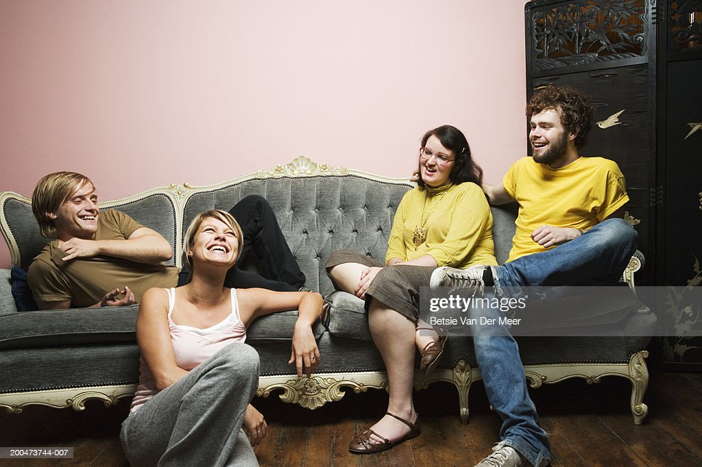 Four friends by sofa : Stock Photo