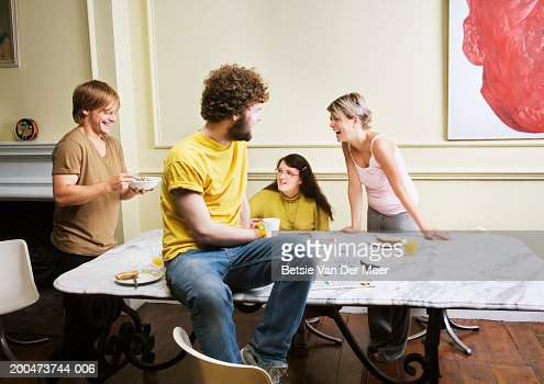 Four friends by table : Stock Photo