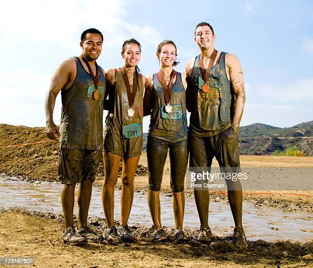 Four friends competing in a mud run(18-25) yrs.