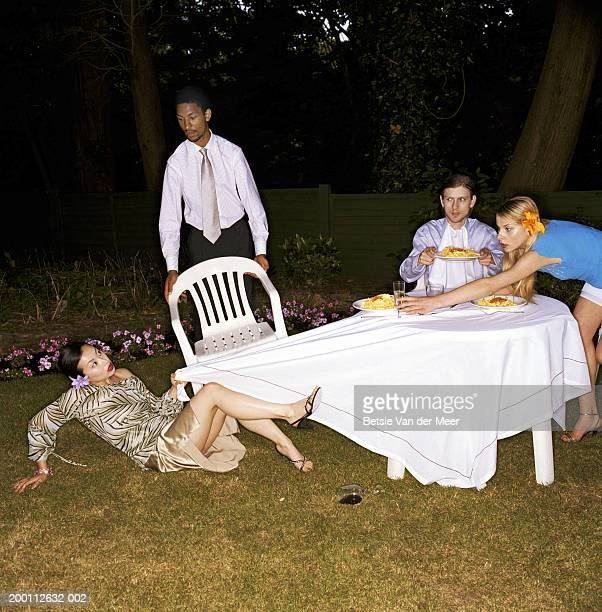 Four friends dining outdoors, woman falling, pulling cloth from table
