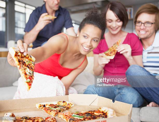 Four friends eating pizza in living room