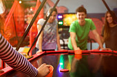 Four friends having fun and playing air hockey game