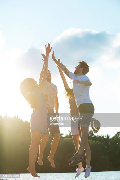 Four friends high fiving at a lake in backlight