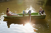 Four friends in a rowboat smiling and relaxing.