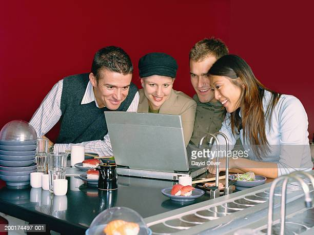 Four friends in sushi restaurant, looking at laptop screen, smiling
