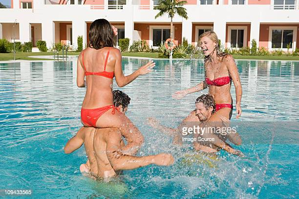 Four friends in swimming pool on vacation, women on men's shoulders