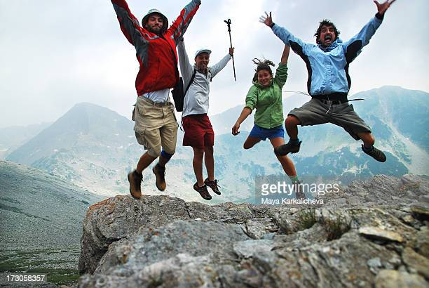 Four friends jumping in mountains