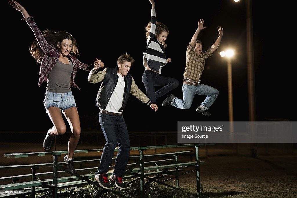 Four friends jumping over bleachers at night : Stock Photo