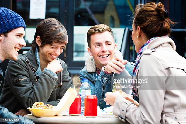 Four friends laughing at one good joke while lunching outdoors