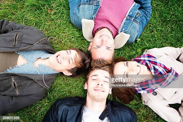 Vier Freunde Leg dich mit dem Rücken auf dem Boden, Lächeln in die Kamera.