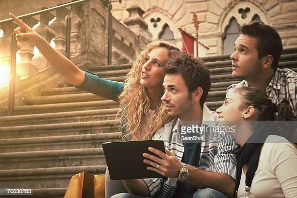 Cuatro amigos mirando algo con un comprimido en sus manos
