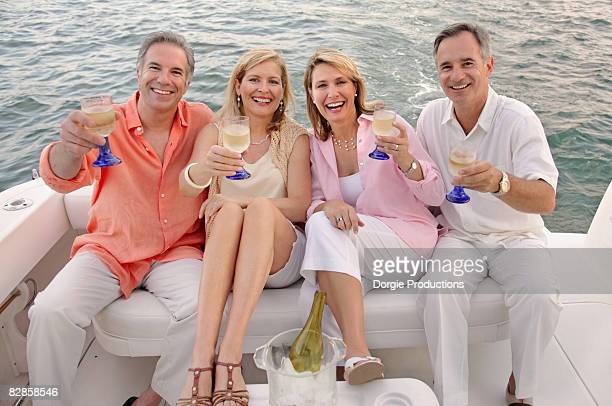 Four friends on a boat cruise enjoying wine