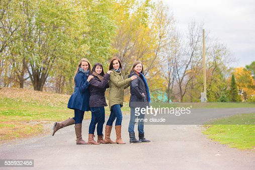 Four friends posing in a park in fall : Stock Photo
