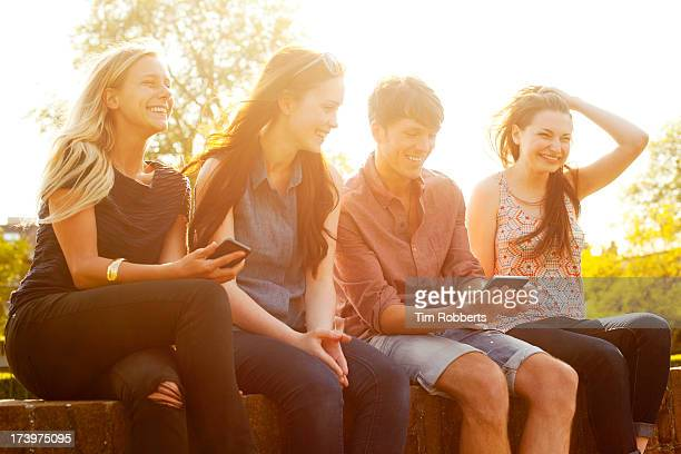 Four friends sat on wall with smart phones.