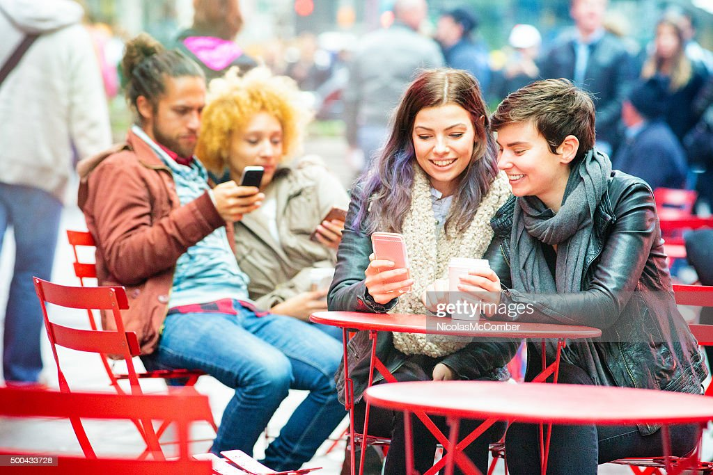 Four friends sending each other text messages outdoors : Stock Photo