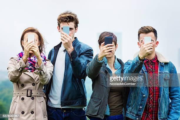 Quatre amis tir mentionné les selfies dans leur téléphone portable
