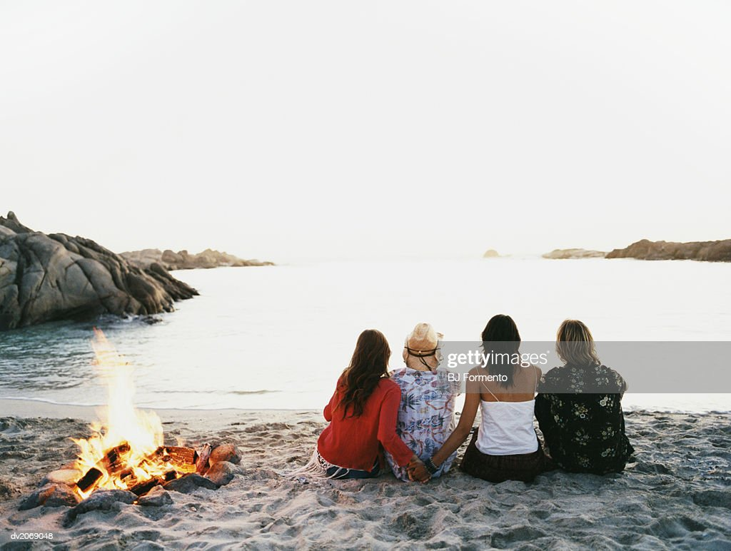 Four Friends Sit on the Beach Next to a Fire Looking at the Sea : Stock Photo