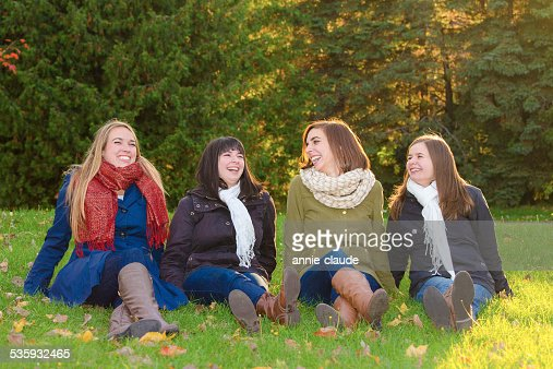 Four friends sitting and laughing in a park in fall : Stock Photo