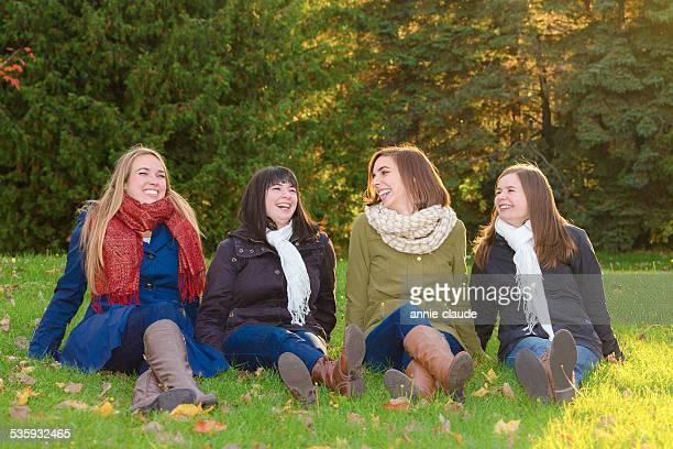 Quatre amis assis et rire dans le parc en automne