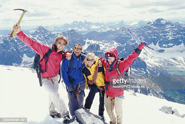 Four friends standing on top of mountain, arms raised