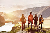 Four friends stands on view point and looking at sunset mountains and river. Adventures travel concept with space for text