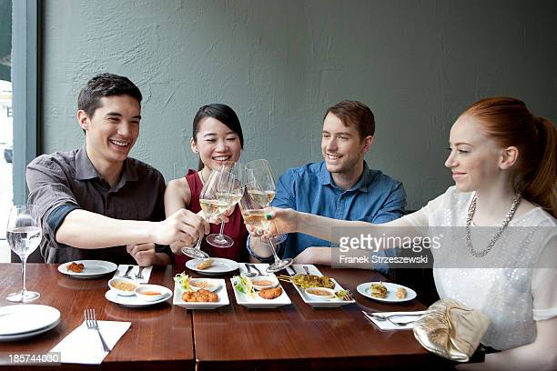 Four friends toasting white wine in restaurant
