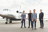 Cheerful young men are standing near airplane and looking at camera with confidence. They are smiling