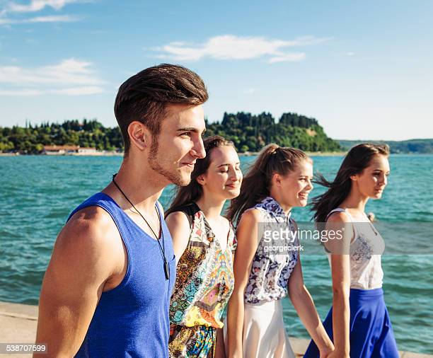 Four friends walking by the sea in summer