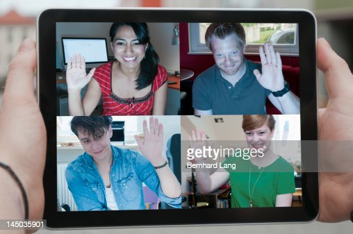 Four friends waving online, displayed on laptop : Stock-Foto
