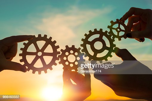 four gears in hands : Stock Photo