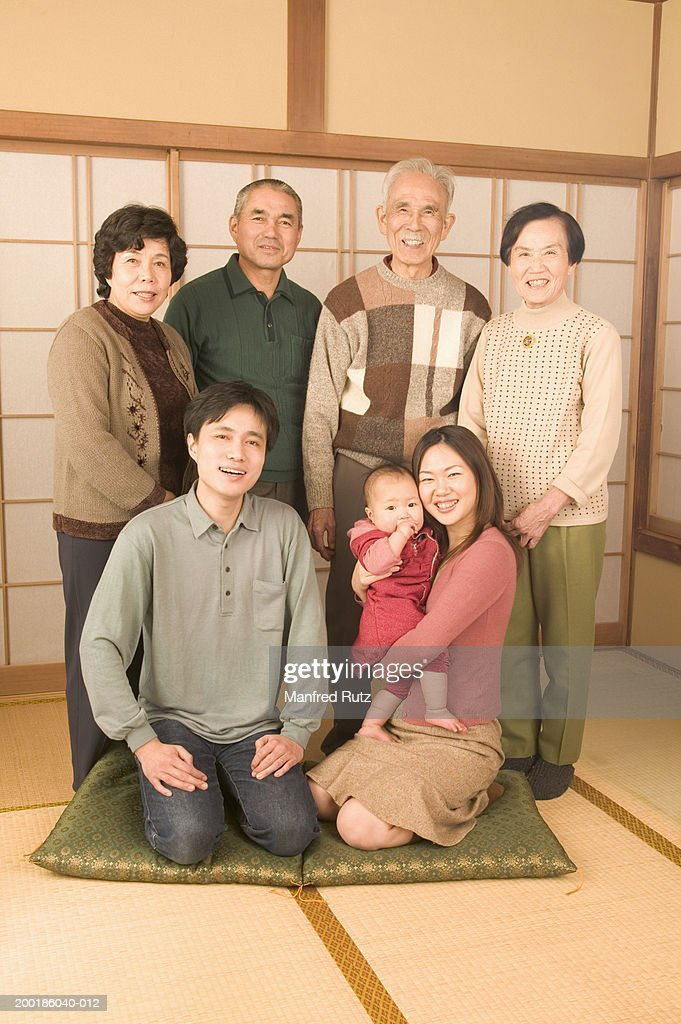 Four generational family indoors, smiling, portrait : Stock Photo
