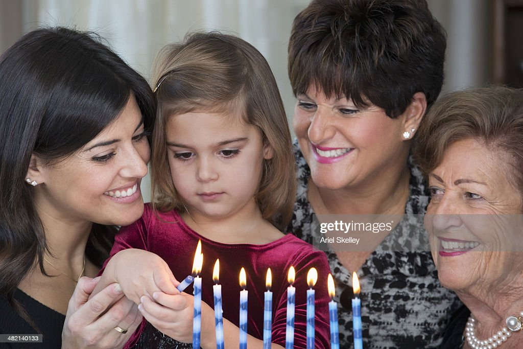 Four generations of women lighting Hanukah menorah
