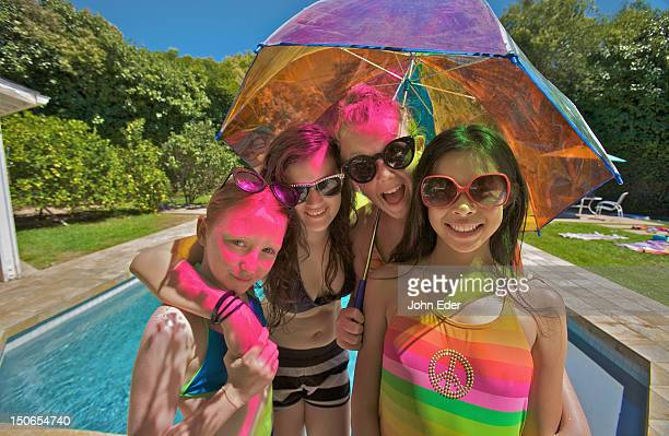 Four girls and a colored umbrella by a pool
