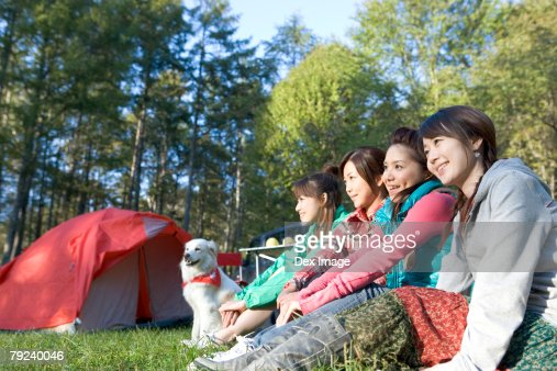 Four girls and a dog sitting on grass : Stock Photo