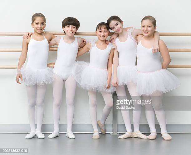 Four girls and boy (8-13) with arms around each other in ballet class